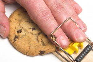 A hand caught in a mousetrap. Dieting concept.